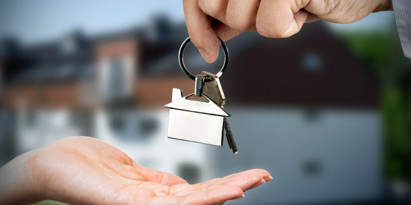 Man gives a woman the keys to a new home. Chrome pedant with house shape